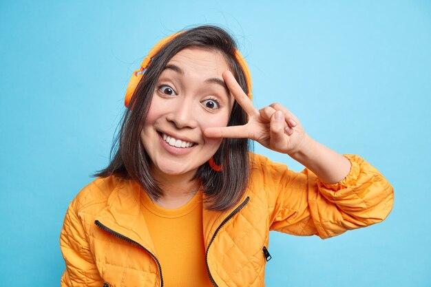 Poziome ujęcie dobrze wyglądającej azjatki uśmiecha się szeroko, pokazuje białe idealne zęby sprawia, że gest pokoju nad okiem cieszy się ulubioną piosenką nosi bezprzewodowe słuchawki na uszach na białym tle nad niebieską ścianą