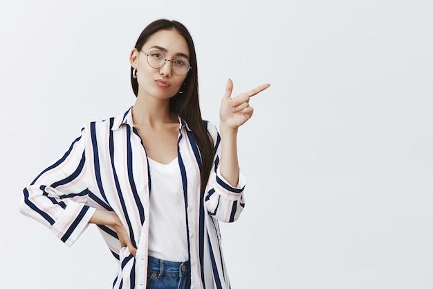 Poziome ujęcie dobrze wyglądającej pewnej siebie i szczęśliwej przedsiębiorczyni stojącej w pewnej siebie kobiecej pozie na szarej ścianie w stylowym stroju, wskazującej w prawo i uroczo składanych ust