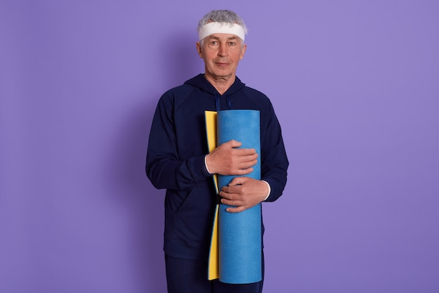 Poziome ujęcie dojrzałego mężczyzny trzymającego w rękach niebieską matę do jogi, patrzącego bezpośrednio na kamerę, ubiera się w stroje