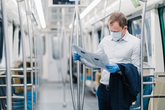 Poziome ujęcie dorosłego mężczyzny nosi formalne ubrania, ochronną maskę medyczną i rękawiczki, czyta prasę, dowiaduje się o epidemiach wirusów, dojeżdża do pracy w transporcie publicznym. koronawirus (covid-19