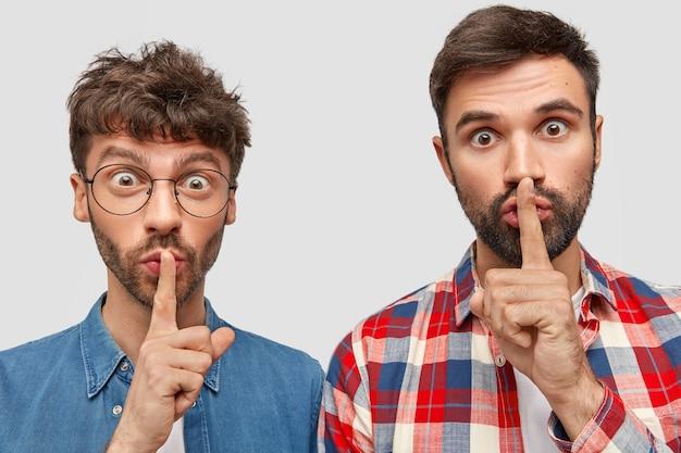 Poziome ujęcie dwóch przystojnych mężczyzn z zaskoczonymi minami, gestem uciszenia, przekazaniem bardzo prywatnych informacji, staniem blisko, pozowaniem przy białej ścianie. ludzie, koncepcja języka ciała