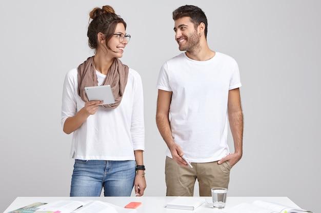 Poziome ujęcie dwóch wesołych młodych kolegów z grupy przygotowujących się do warsztatów