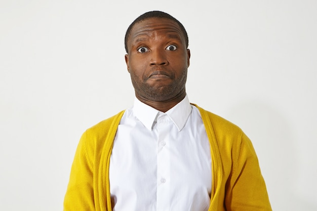 Poziome ujęcie emocjonalnego faceta z afroamerykaninem, który ma na sobie żółty sweter na białej koszuli i ma zdziwiony wygląd, unosząc brwi, zszokowany nieoczekiwanymi wiadomościami,