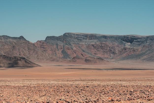 Poziome ujęcie górskiego krajobrazu na pustyni namib w namibii pod błękitnym niebem