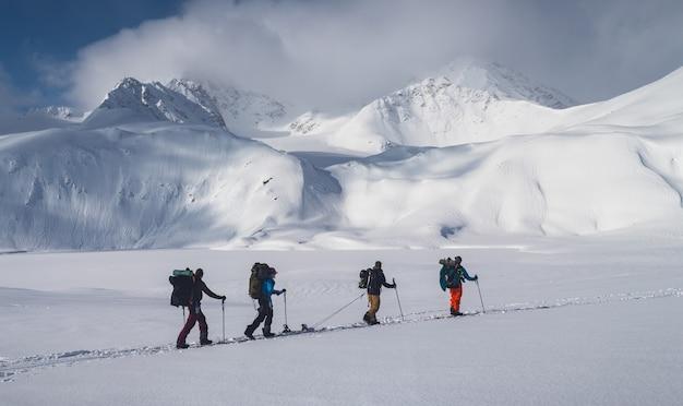 Poziome ujęcie grupy ludzi wędrujących po górach pokrytych śniegiem pod zachmurzonym niebem