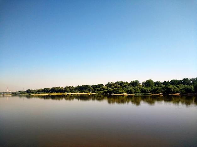 Poziome ujęcie jeziora i gęstych lasów na jego brzegu w warszawie