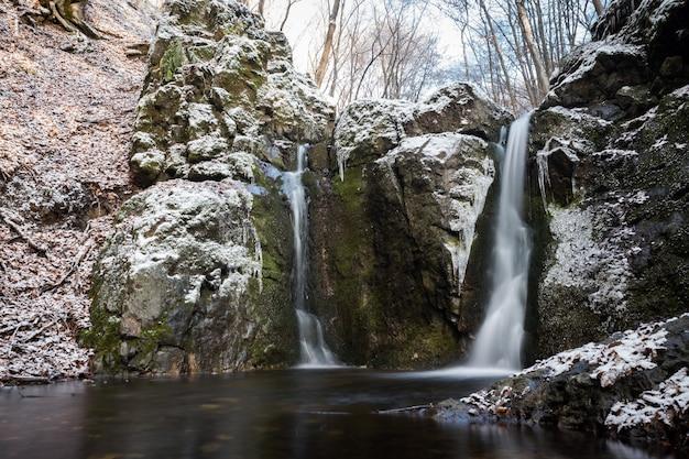 Poziome ujęcie kilku wodospadów wychodzących z ogromnych ośnieżonych skał w sezonie zimowym