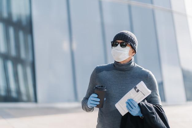 Poziome ujęcie mężczyzny w niebezpieczeństwie zarażenia koronawirusem w miejscu publicznym, chroni się w masce medycznej i gumowych rękawiczkach, pije kawę na wynos, patrzy gdzieś przez okulary przeciwsłoneczne