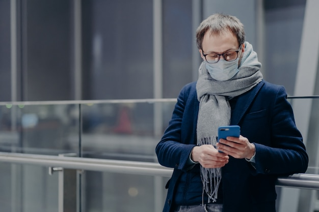 Poziome ujęcie mężczyzny w okularach używa nowoczesnego telefonu komórkowego, nosi maskę medyczną podczas wybuchu koronawirusa, ma ochronę przed grypą w dużym centrum handlowym. sezon na grypę i koronę. pojęcie opieki zdrowotnej