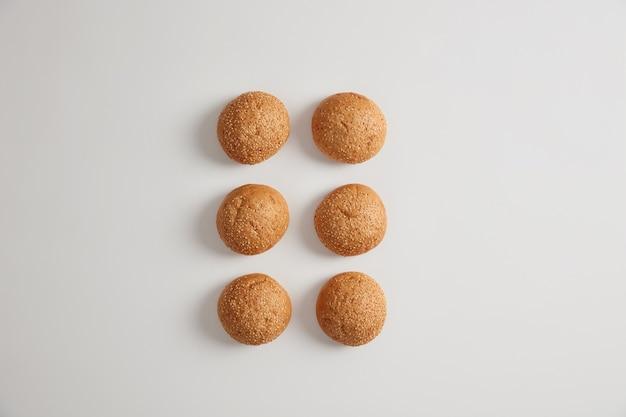 Poziome ujęcie miękkich, małych okrągłych bułeczek sezamowych burger do przygotowania pysznych hambrugers lub kanapek. odżywcze chrupiące brioszki na białej powierzchni. fast food, niezdrowe jedzenie.