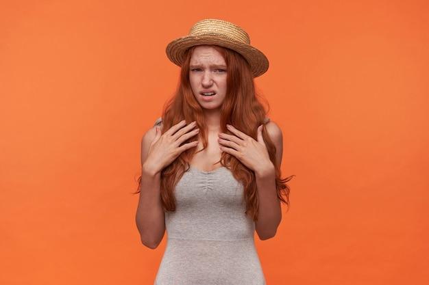 Poziome ujęcie młodej atrakcyjnej kobiety z falistymi rudymi włosami w codziennych ubraniach, trzymając ręce na piersi i patrząc na kamery z dąsaniem, pokazując wstręt i marszczące się czoło