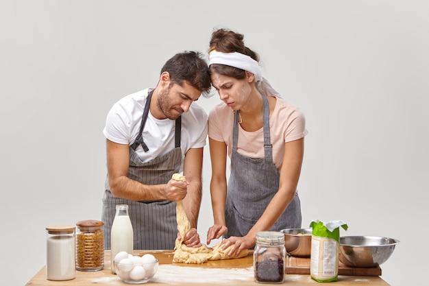 Poziome ujęcie niedoświadczonej pary przygotowuje lepkie ciasto po raz pierwszy, będąc złym kucharzem, wygląda niezręcznie, nosi fartuchy, stań przy stole z produktami. katastrofa w kuchni i awaria gotowania