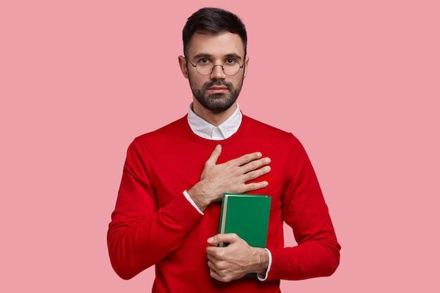 Poziome ujęcie nieogolonego, poważnego męskiego studenta, który obiecuje ciężką naukę, trzyma zielony podręcznik, nosi czerwony elegancki sweter