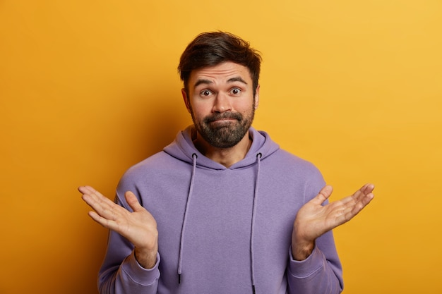 Poziome ujęcie nieświadomego, brodatego mężczyzny rasy kaukaskiej rozkłada dłonie na boki, wzrusza ramionami, mierzy się z dylematem, dokonuje wyboru, nosi swobodną bluzę, wygląda z powątpiewaniem, pozuje na żółtej ścianie