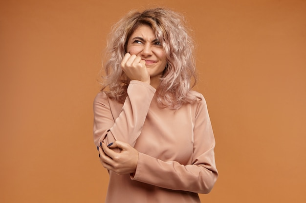 Poziome ujęcie niezadowolonej młodej kobiety ze stylową fryzurą wykrzywiającą się, trzymając dłoń na policzku, mającej bolesny wygląd, cierpiącej z powodu strasznego bólu zęba