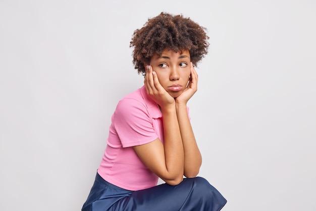 Poziome ujęcie niezadowolonej smutnej kobiety ma zamyślony, żałosny wyraz ubranej w koszulkę i spódnicę, pochyla się na dłoniach skoncentrowanych na białym tle nad białą ścianą