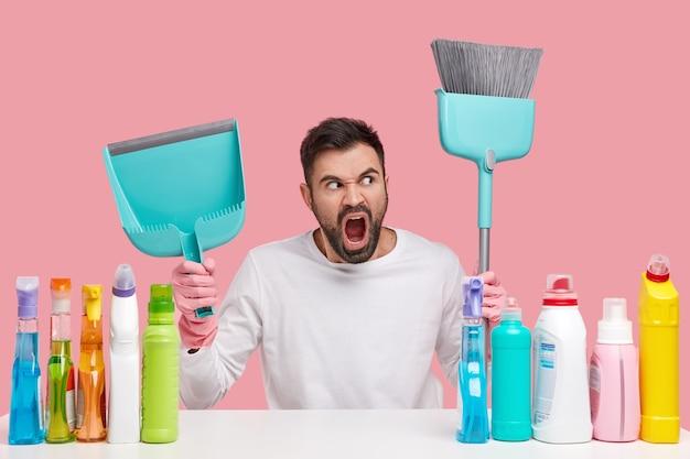 Poziome ujęcie oburzonego mężczyzny z grubą brodą, niosącego miotłę i miarkę, wrzeszczącego gniewnie, ubranego w białe szaty, wściekłego za dużo pracy