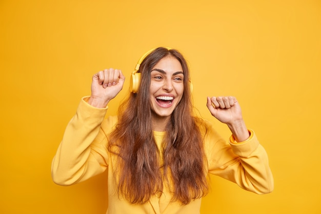 Poziome ujęcie optymistycznej ciemnowłosej kobiety używa słuchawek porusza się ciało cieszy się nową playlistą wesoły wyraz lubi melodię nosi żółtą kurtkę uśmiecha się szeroko ma dobrą zabawę