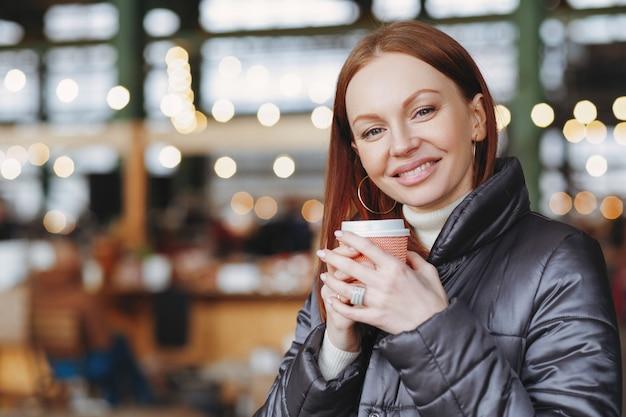 Poziome ujęcie pięknej kobiety z zębatym uśmiechem, trzyma papierową filiżankę napoju, cieszy się aromatyczną kawą
