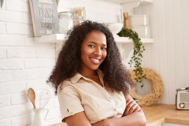 Poziome ujęcie pięknej młodej czarnej kobiety mulat w beżowej koszuli skrzyżowanej ramionami na klatce piersiowej, patrząc z pewnym siebie uśmiechem, pozuje w pomieszczeniu przed stylowym wnętrzem kuchni