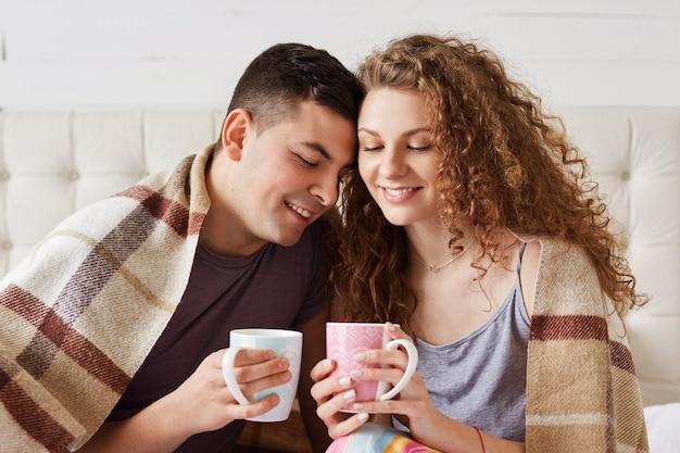Poziome ujęcie pięknej młodej kobiety i jej chłopaka, ciesz się poranną kawą na łóżku, spróbuj się ogrzać po spacerze