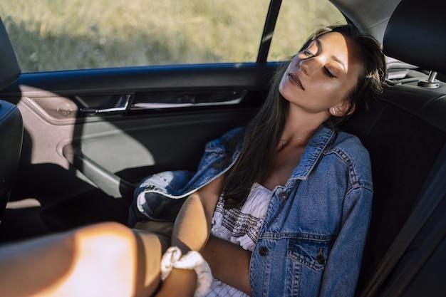 Poziome ujęcie pięknej młodej kobiety rasy kaukaskiej stwarzających na tylnym siedzeniu samochodu na polu