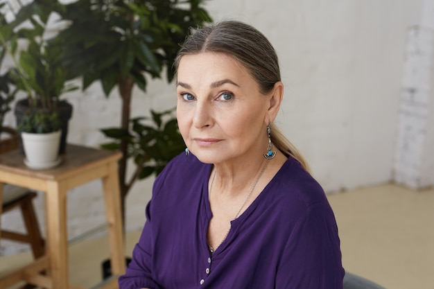 Poziome ujęcie pięknej niebieskookiej babci o europejskim wyglądzie relaksującej się w domu, czekającej na wnuki, noszącej fioletową swobodną koszulę i kolczyki, z poważnym wyrazem twarzy