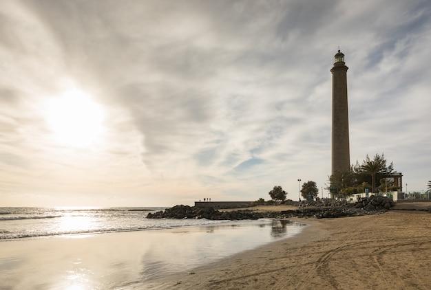 Poziome ujęcie pięknej plaży w maspalomas, z latarnią morską faro de maspalomas lub maspalomas, gran canaria, hiszpania