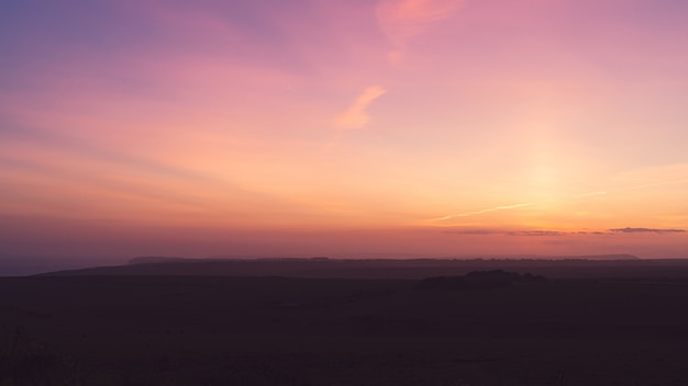 Poziome ujęcie pola pod zapierającym dech w piersiach fioletowym niebem