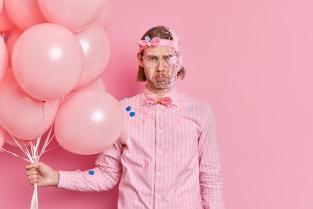 Poziome ujęcie ponurego, przygnębionego europejczyka wygląda na zdenerwowanego z przodu trzyma kilka nadmuchanych balonów posmarowanych serpentynowym sprayem, nosi świąteczne ubrania odizolowane na różowej ścianie