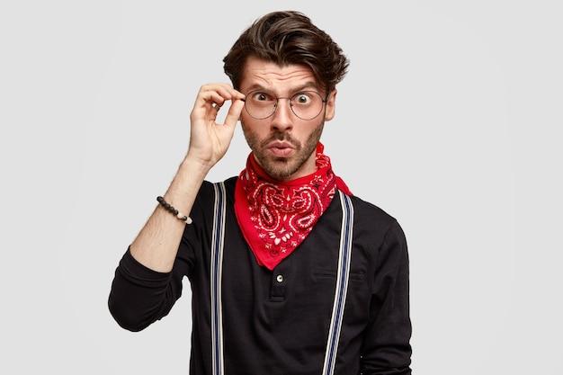 Poziome ujęcie poważnego, brodatego młodego mężczyzny z modną fryzurą, uważnie patrzy przez okulary, ubrane w modne ubrania, widzi coś z przodu, odizolowane na białej ścianie
