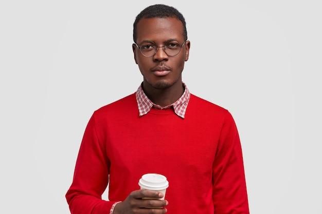 Poziome ujęcie poważnego ciemnoskórego mężczyzny trzyma jednorazową filiżankę kawy, ubrany w czerwony sweter, wygląda pewnie