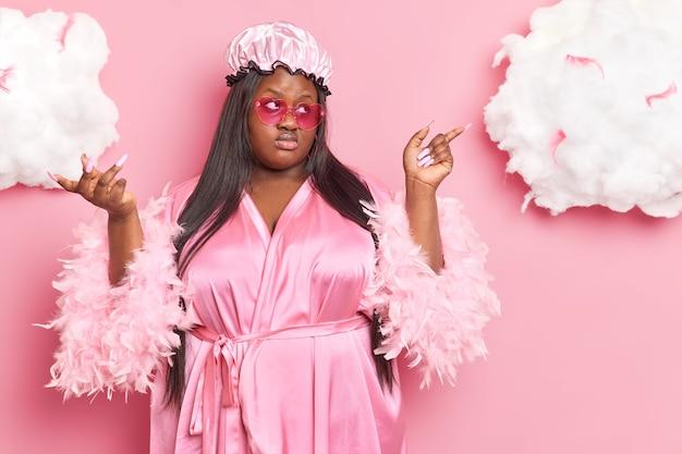 Poziome Ujęcie Poważnej Afroamerykanki Z Długimi Ciemnymi Włosami Wskazuje Na To, że Pokazuje Coś Na Bok Darmowe Zdjęcia