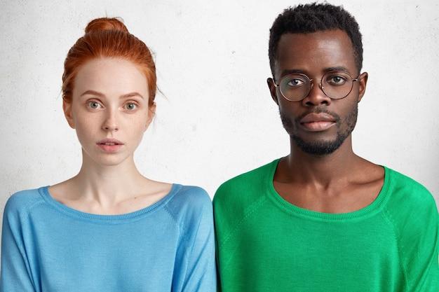 Poziome ujęcie poważnej rudej samicy i jej ciemnoskórej najlepszej przyjaciółki w okularach, stojących obok siebie
