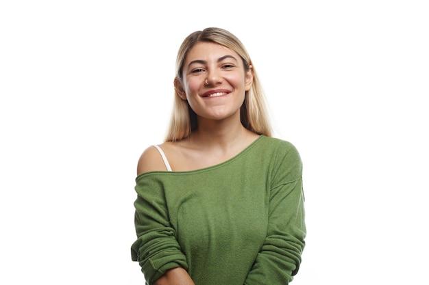 Poziome ujęcie pozytywnej młodej europejskiej studentki z kolczykiem w nosie i farbowanymi włosami, pozującej, patrzącej z radosnym, czarującym uśmiechem, czującej się zrelaksowanym po wykładach na uniwersytecie