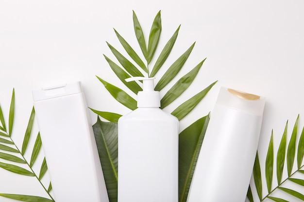 Poziome ujęcie produktów kosmetycznych na tle zieleni lub liści.