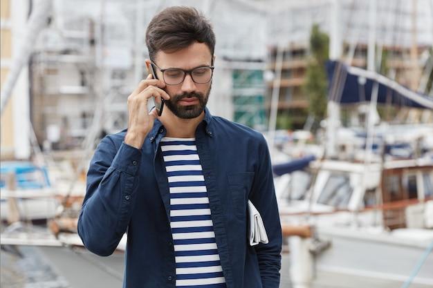 Poziome ujęcie przemyślanego faceta rozmawia przez telefon