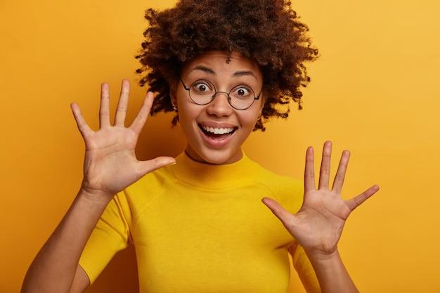 Poziome ujęcie przyjemnie wyglądającej szczęśliwej kobiety unosi dłonie, ma zadowoloną, wesołą minę, patrzy figlarnie, nosi okulary i żółtą koszulkę, bawi się z dzieckiem