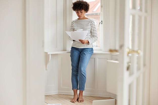 Poziome ujęcie przyjemnie wyglądającej, zapracowanej młodej kobiety studiuje przepisy podatkowe, trzyma dokumenty,