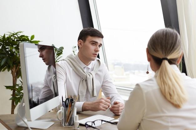 Poziome ujęcie przystojnego młodego człowieka rekrutującego brunetki w stylowych, formalnych strojach, przeprowadzając rozmowę kwalifikacyjną z nierozpoznawalną dojrzałą kandydatką do pracy, uważnie słuchając jej w nowoczesnym wnętrzu biurowym