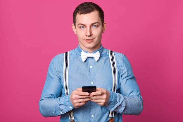 Poziome ujęcie przystojnego młodego faceta trzyma telefon komórkowy, patrzy ze spokojnym wyrazem twarzy, mężczyzna nosi koszulę, szelki, białą muszkę, pozy na różowej ścianie