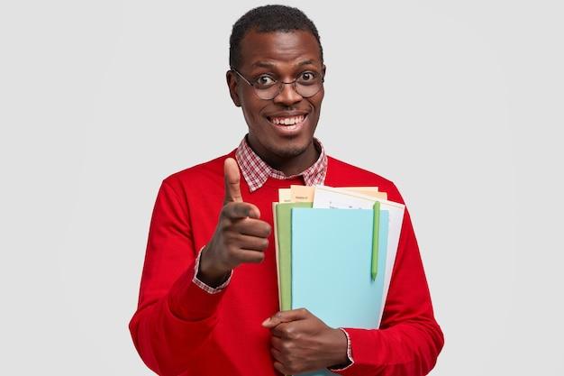 Poziome ujęcie przystojny uśmiechnięty młody człowiek sprawia, że gest pistoletu, ubrany w czerwony sweter dorywczo, będąc w dobrym nastroju