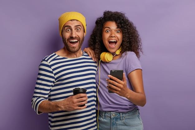 Poziome ujęcie radosnej, różnorodnej pary spędzającej razem czas, oglądając zabawne filmy z sieci społecznościowych, szeroko przytulaj się i otwieraj usta, podekscytowani niesamowitym trafem, używaj smartfona, pij kawę