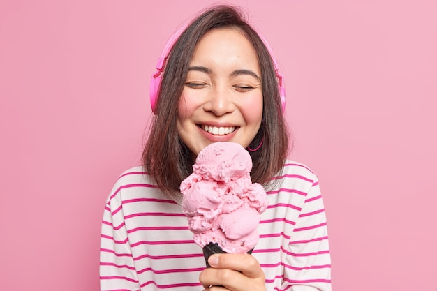 Poziome ujęcie radosnej ślicznej azjatyckiej tysiącletniej kobiety zamyka oczy z przyjemności jedząc smaczne słodkie lody lubi letni deser słucha muzyki używa bezprzewodowych słuchawek cieszy się weekendem