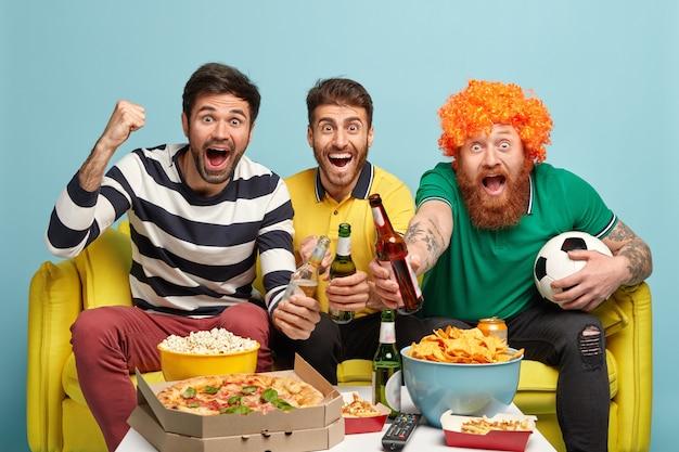 Poziome ujęcie radosnych trzech mężczyzn spotykających się w weekend, aby obejrzeć mecz piłki nożnej, świętować gol, siedzieć na żółtej kanapie, odizolowane na niebieskiej ścianie. ludzie, koncepcja emocji