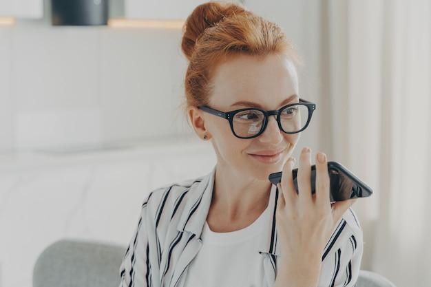 Poziome ujęcie rudej kobiety używa asystenta głosowego na smartfonie wykonuje połączenie głosowe