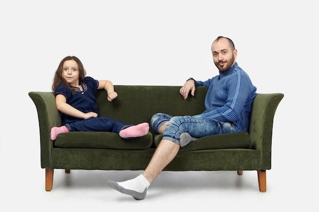 Poziome ujęcie śmiesznej uczennicy siedzącej na zielonej sofie z brodatym ojcem w zwykłych ubraniach i wpatrującej się w kamerę z emocjonalnymi zszokowanymi wyrazami na tle białej ściany