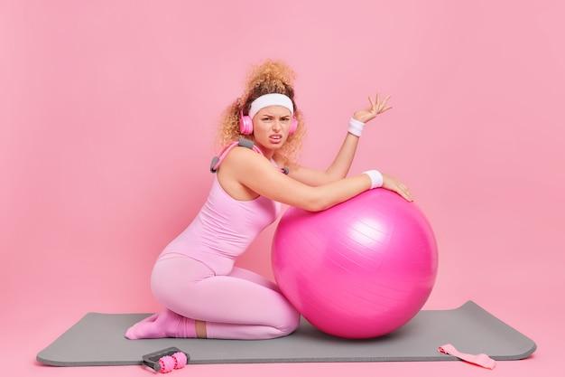 Poziome ujęcie sportowej kobiety o kręconych włosach nosi opaski na nadgarstki i body
