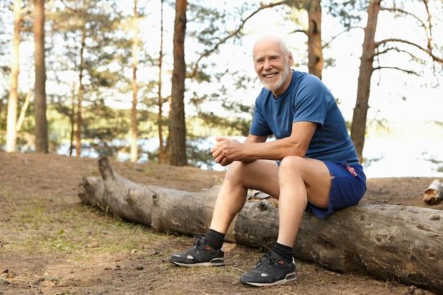 Poziome ujęcie szczęśliwego wesołego starszego emeryta z grubą białą brodą siedzącego na zwalonym drzewie w lesie, śmiejącego się radośnie, odpoczywającego po intensywnym porannym treningu cardio, w trampkach