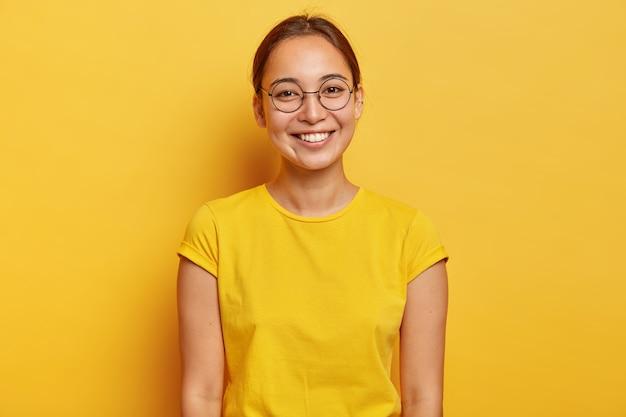 Poziome ujęcie szczęśliwej azjatyckiej studentki nosi duże okrągłe okulary, żółte ubranie codzienne, uśmiecha się delikatnie, zadowolona po udanym dniu na uniwersytecie, ubrana w letnią żółtą koszulkę